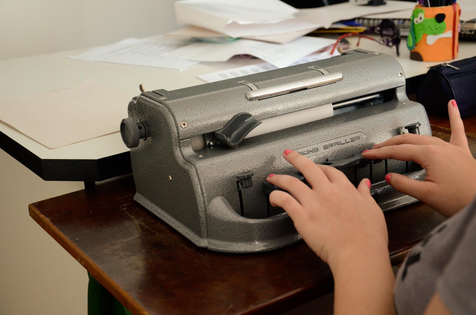 a imagem dá corte nas mãos de uma aluna teclando na máquina de braille. A máquina é cinza e está sobre uma mesa de madeira na cor marrom escuro, em primeiro plano. Em segundo plano, atrás desta mesa, está outra mesa, na cor branca, com papéis e outros materiais de escola sobre ela.