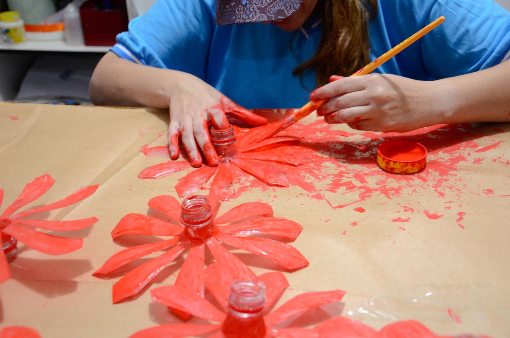 a imagem mostra as mãos de uma aluna pintando de vermelho garrafas pet cortadas em formato de flores. Ela está sentada a uma mesa coberta com papelão marrom. Tem as mãos sujas de tinta. A mão direita está sobre a mesa, com o dedo indicador dentro de um pequeno pote de tinta. A mão esquerda segura um pincel sobre uma das pétalas. À frente da estudante há três flores já pintadas de vermelho.a imagem mostra as mãos de um aluno apertando um jogo de pinos coloridos e com tamanhos diferentes.a imagem mostra as mãos de uma aluna pintando de vermelho garrafas pet cortadas em formato de flores. Ela está sentada a uma mesa coberta com papelão marrom. Tem as mãos sujas de tinta. A mão direita está sobre a mesa, com o dedo indicador dentro de um pequeno pote de tinta. A mão esquerda segura um pincel sobre uma das pétalas. À frente da estudante há três flores já pintadas de vermelho.