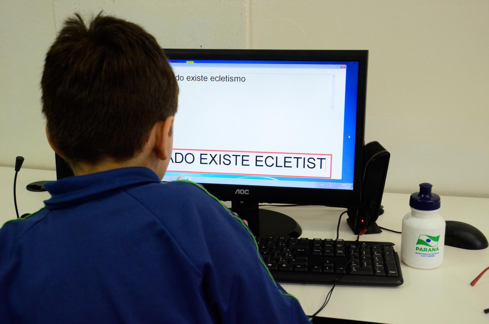 a imagem mostra um aluno criança de costas, sentado de frente para um computador, que tem texto sendo mostrado na tela.