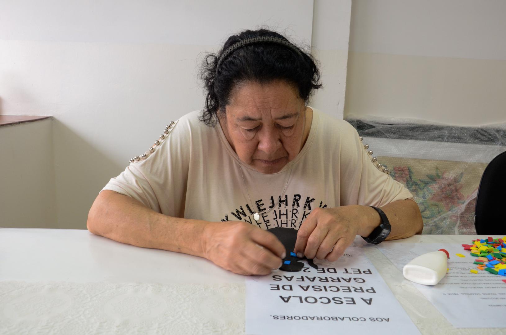 a imagem mostra uma senhora sentada a uma mesa branca, fazendo colagem sobre um papel branco com texto. Ela está utilizando as duas mãos na atividade, está olhando para baixo, concentrada.