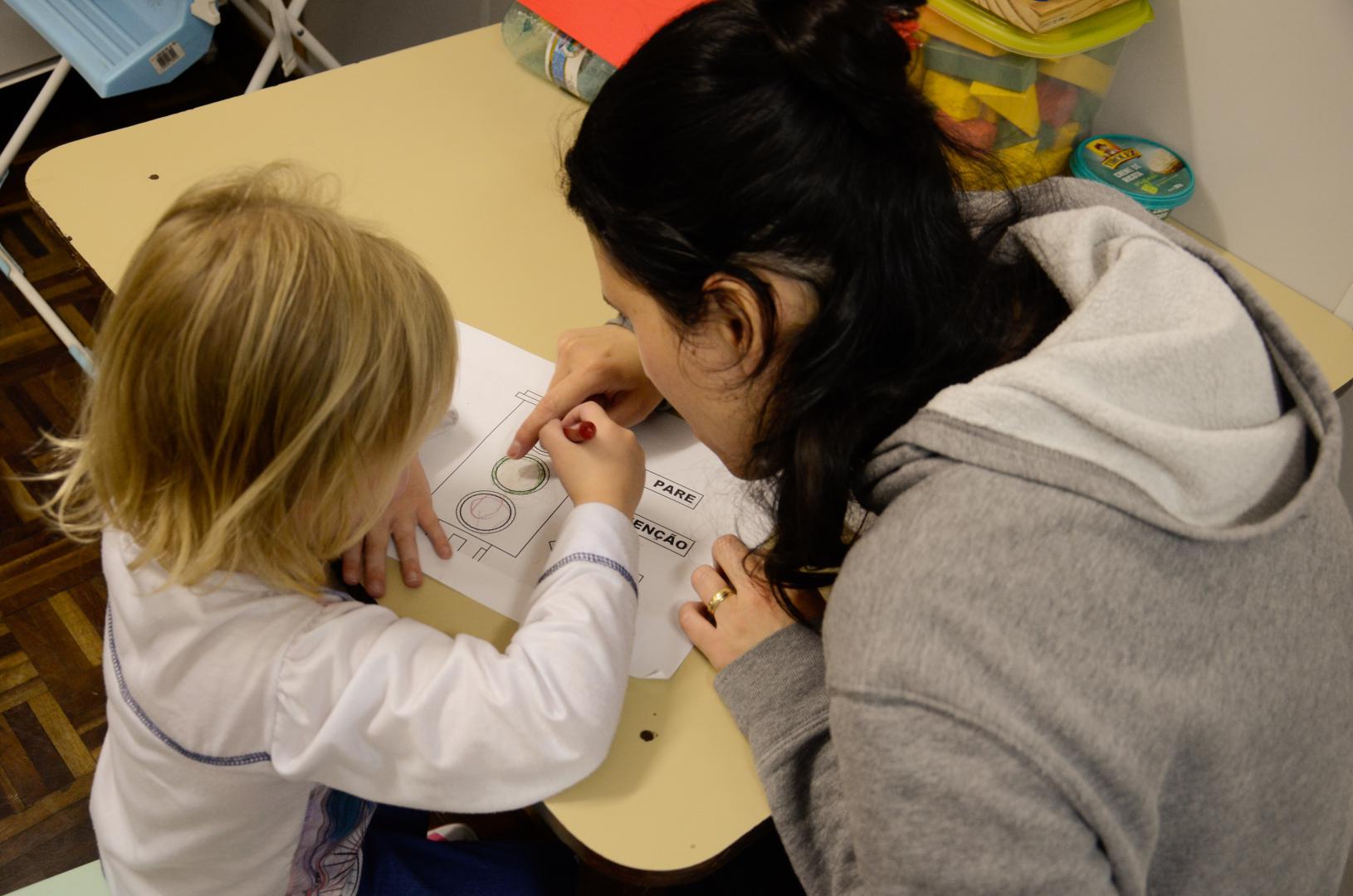 a imagem em ângulo de cima para baixo mostra uma aluna criança, à esquerda, sentada a uma mesa bege ao lado da professora, à direita, ambas de costas para a foto. A estudante tem o braço esquerdo apoiado até o cotovelo na mesa, sobre o papel em que realiza a atividade. A mão direita dela segura um lápis de cor. A professora aponta para o desenho no papel utilizando a mão direita.