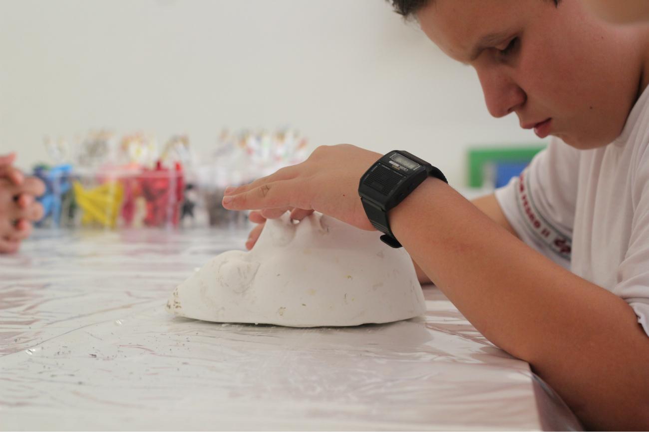 a imagem mostra, à direita, um aluno tateando um rosto feito em gesso branco. O corte da imagem é no rosto do adolescente e nas mãos dele sobre a peça, que está sobre uma mesa branca. Ele tem os olhos fechados.