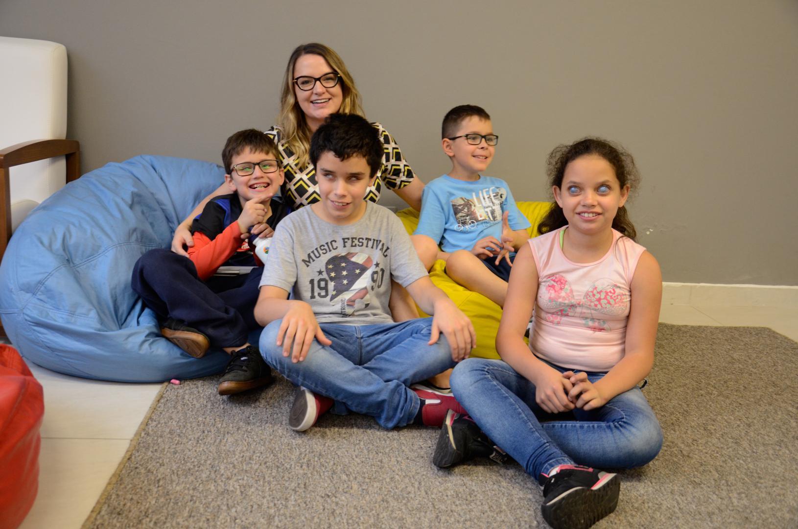 a imagem mostra a coordenadora do projeto, Diele Pedrozo Santo, com três alunos e uma aluna, todos crianças, sentados no chão sobre um tapete cinza, alguns num puf azul e outro num puf amarelo. Ela abraça dois alunos que estão ao lado dela. Todos sorriem.